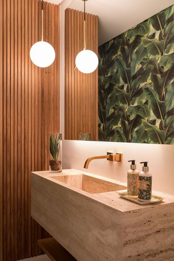 a tropical bathroom with a wood slab accent wall, a large mirror, a tropicla leaf wall, a stone floating sink and a bold pendant lamp