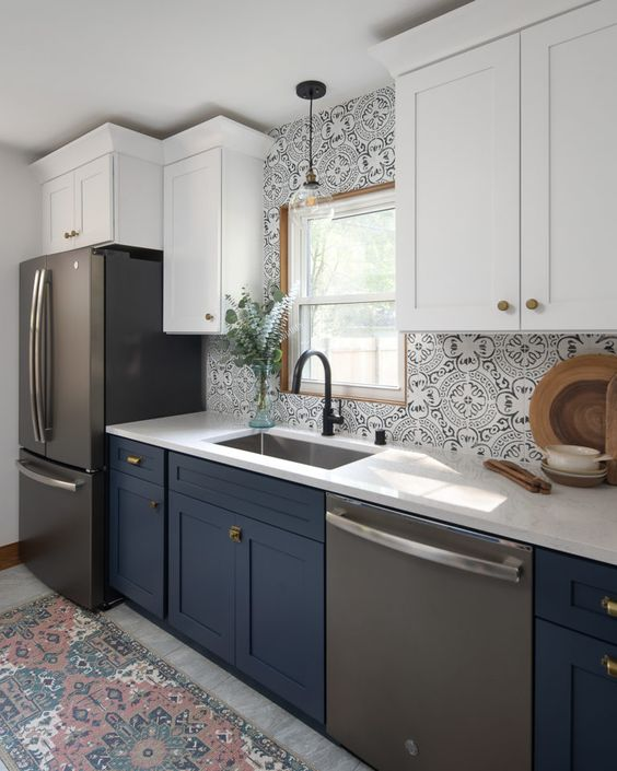 a two-tone kitchen with white and navy cabinets, chic Moroccan tiles on the backsplash, a rug that echoes with them