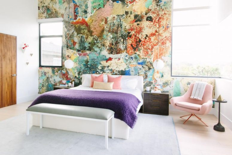 a unique bedroom with small windows, a statement colorful wall, a white bed and colorful bedding, a pink chair and a side table