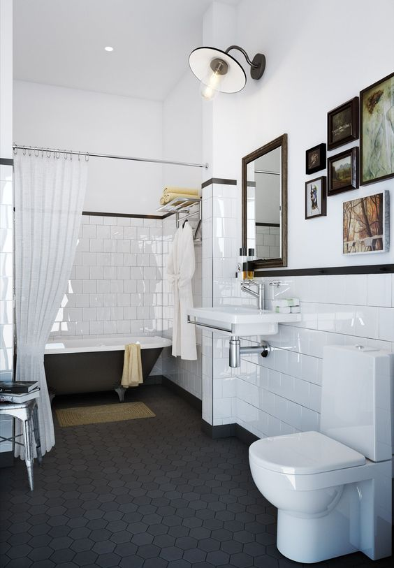 a vintage bathroom with a black hex tile floor, planked walls and white square tiles, a black clawfoot tub, a gallery wall and a floating sink is chic