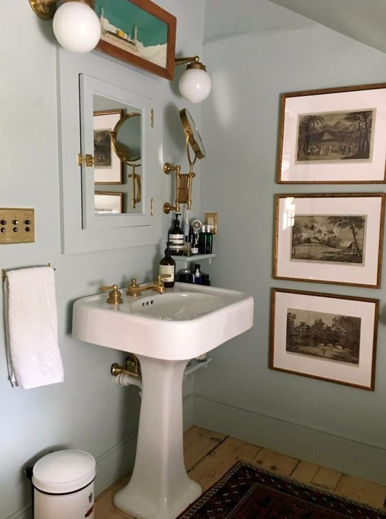 a vintage bathroom with light blue walls, a built-in storage cabinet, a pedestal sink, a vintage gallery wall, gold touches and fixtures and shelves