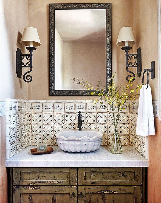 a vintage bathroom with tan and peachy walls, pretty patterned tiles, a shabby chic vanity with a refined stone vessel sink and vintage sconces