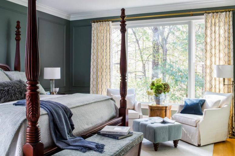 a vintage bedroom with grey paneled walls, a rich-stained cnaopy bed, white chairs, a blue ottoman and a view of the forest
