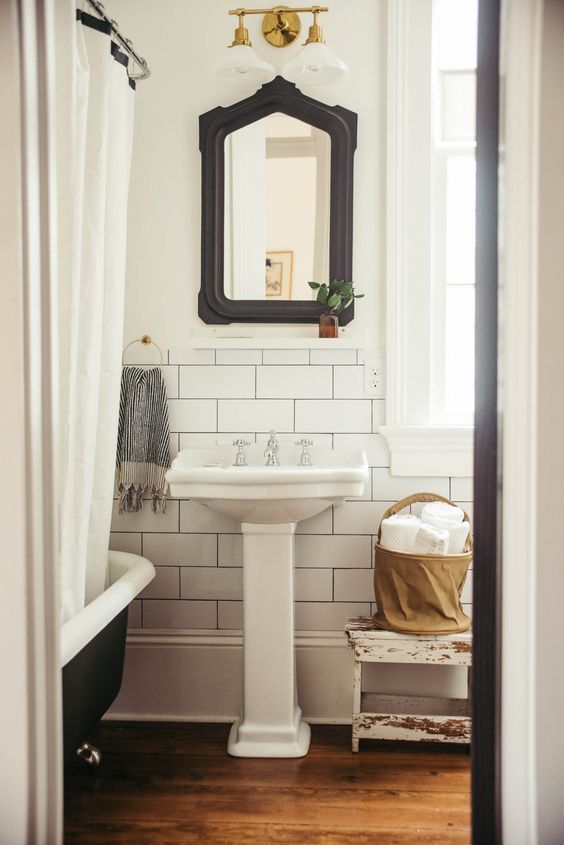 a vintage black and white bathroom clad with subway tiles, with a mirror in a black frame, a black clawfoot tub, a pedestal sink and a basket for storage