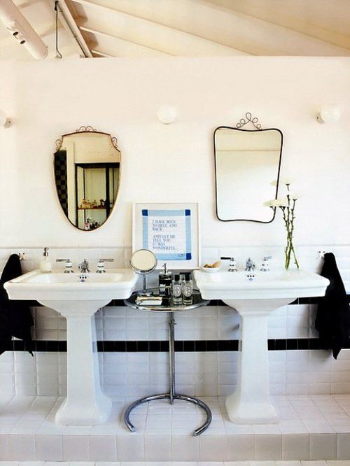 a vintage black and white bathroom with two pedestal sinks, black and white tiles, mismatching mirrors, a side table with various stuff