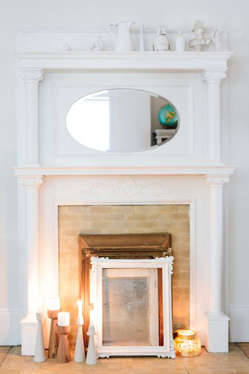 a vintage built-in fireplace with a white mantel, a mirror and some mirrors, frames and candles on display is very chic