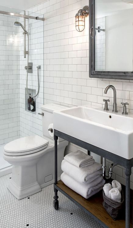 a vintage farmhouse bathroom clad with penny and subway tiles, a console sink, a shower space and a mirror cabinet