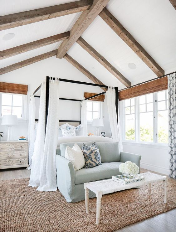 a vintage farmhouse bedroom with wooden beams, a canopy bed and a blue sofa, a large rug and printed curtains