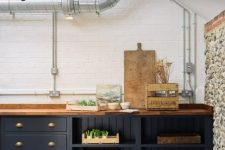 a vintage farmhouse kitchen with navy cabinets, wooden beams, a stone accent wall and rich-stained countertops and pendant lamps