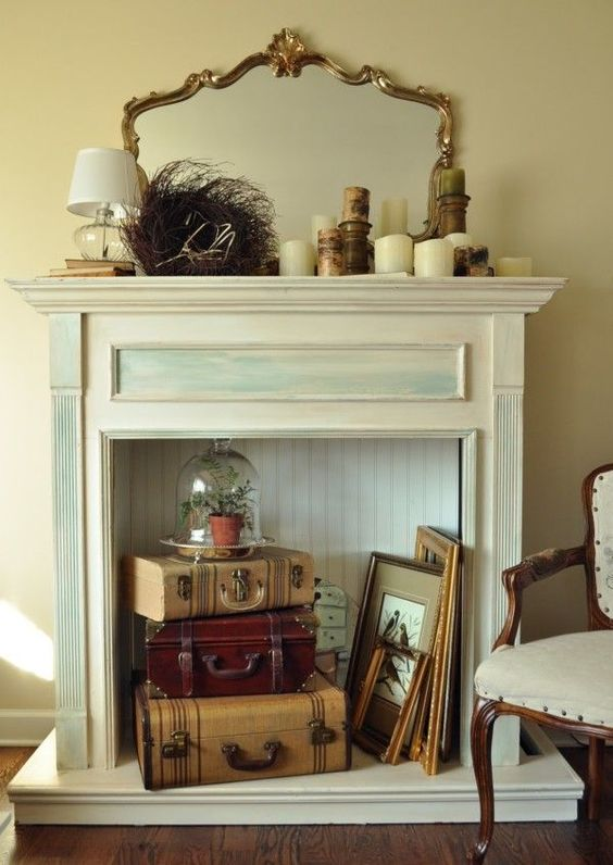 a vintage faux fireplace with artworks, frames and vintage suitcases, a refined mirror in a gilded frame, candles and a table lamp