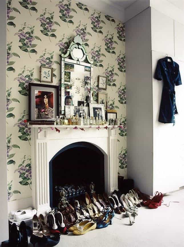 a vintage fireplace used for storing shoes and a mantel used for a pretty and bold gallery wall