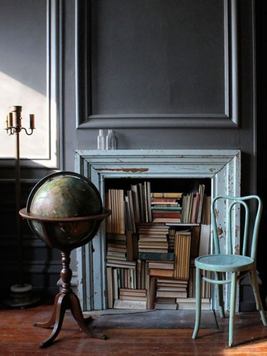 a vintage fireplace with a blue shabby chic mantel, books and a blue chair, a globe is a stylish and cool idea
