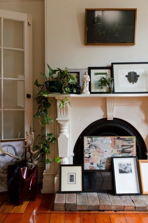 a vintage fireplace with an arrangement of artworks, with potted plants and a statue is a beautiful idea for a refined feel