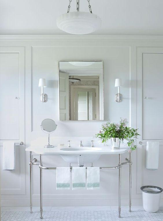 a vintage neutral bathroom with a large console sink, white penny tiles, a pendant lamp on chain and a bucket with blooms