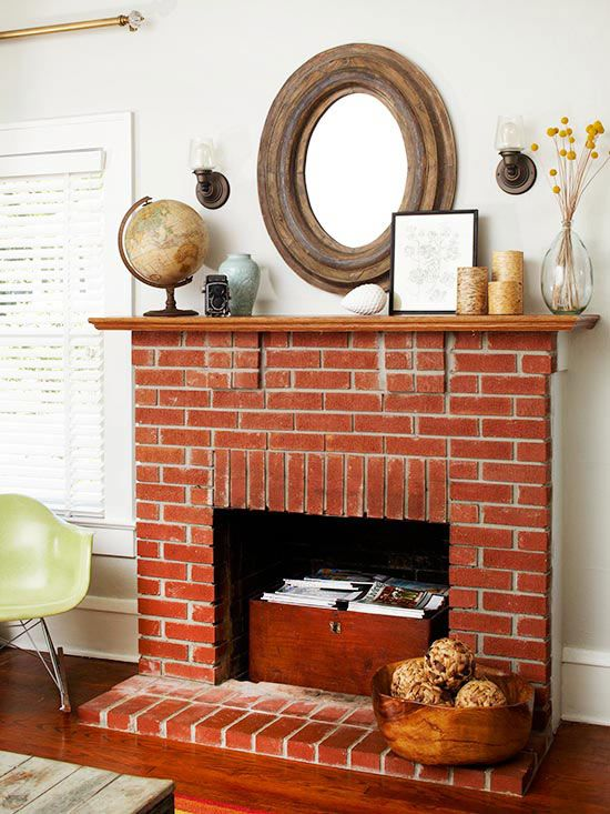 a vintage red brick fireplace with a wooden chest that is used for books and magazine storage, with pretty vintage decor on the mantel