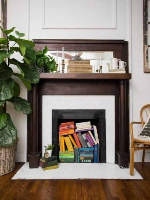a vintage space with a fireplace, with a dark stained mantel, with colorful books inside to make a bold accent and a statement plant