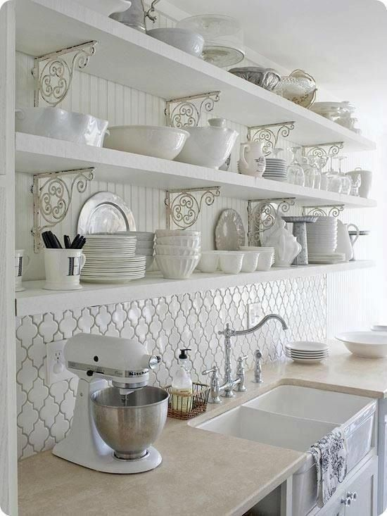 a vintage white kitchen with open shelves, a white arabesque tile backsplash, neutral stone countertops and silver fixtures is very refined