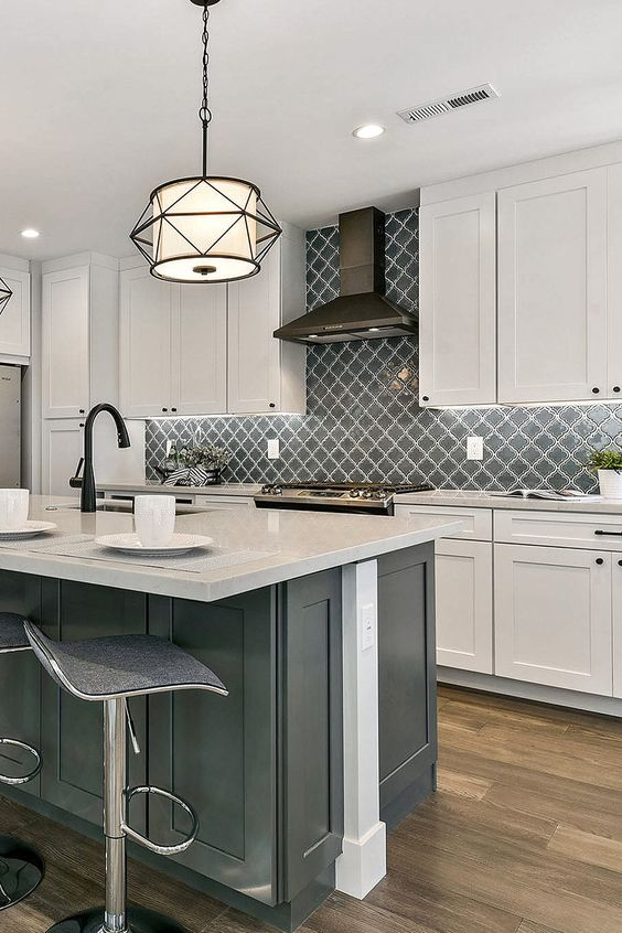 a vintage white kitchen with shaker cabinets, a grey kitchen island, white stone countertops, black fixtures and appliances and a grey arabesque tile backsplash