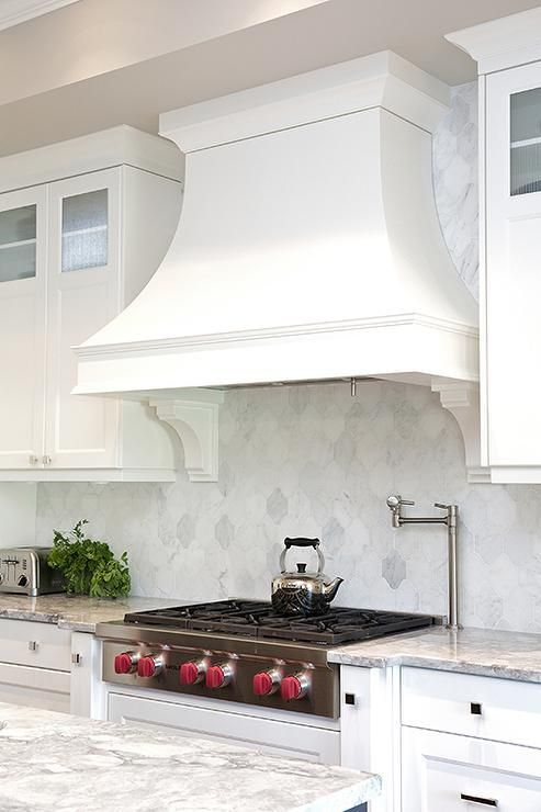 a vintage white kitchen with shaker cabinets, a large vintage hood, a white marble arabesque tile backsplash and cool appliances