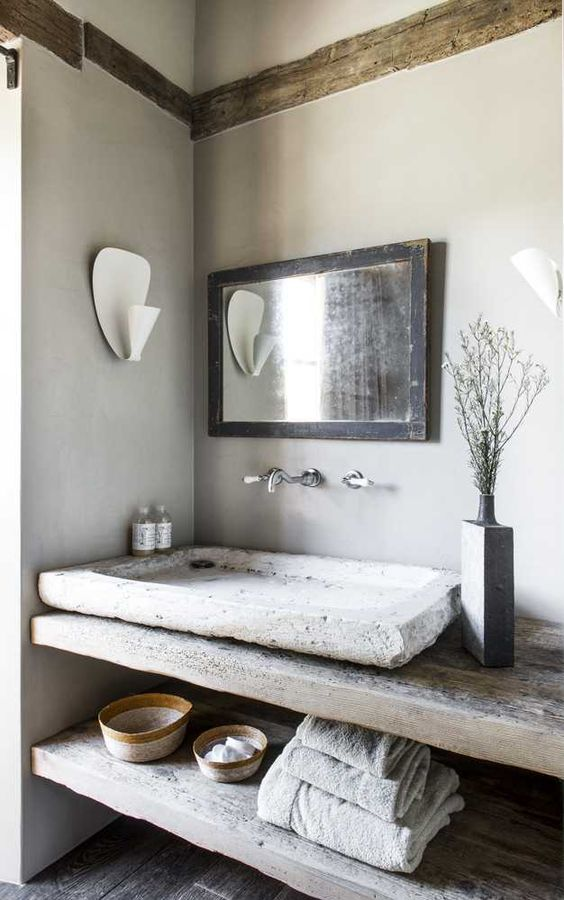 a wabi-sabi bathroom with concrete walls and a wooden floor, a shabby chic reclaimed wood vanity and a stone vessel sink plus a mirror in a shabby chic frame