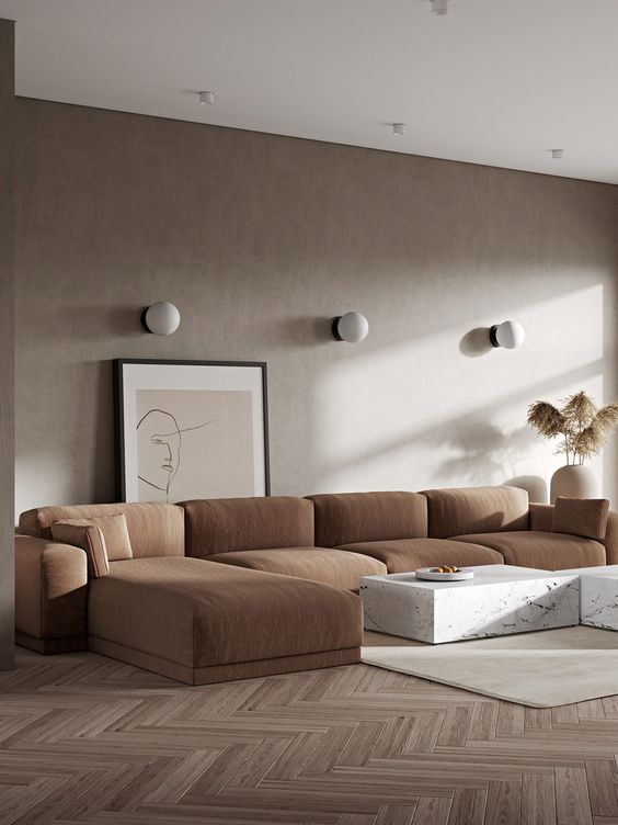 a warm-toned neutral living room with taupe walls, a rust-colored sectional, white marble coffee tables and wall lamps