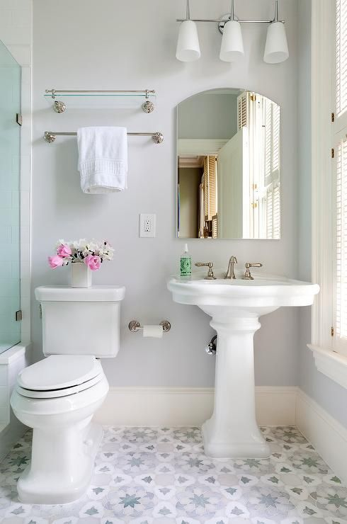 a welcoming and airy bathroom with light blue walls, a shower space, a pedestal sink, sconces and an arched mirror is a chic space