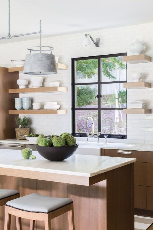 a welcoming light-stained kitchen with white stone countertops and a tile wall, thick floating shelves and elegant fixtures