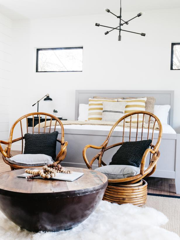a welcoming mid-century modern bedroom with small windows, a grey bed, printed bedding, rattan chairs, a round coffee table and a cool chandelier