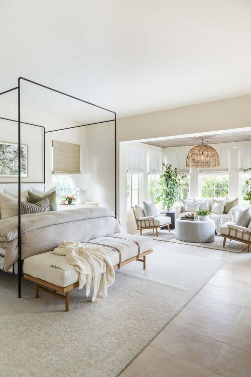 a welcoming neutral farmhouse bedroom with a canopy bed, an upholstered bench, a sitting zone with a sofa, chairs and an ottoman