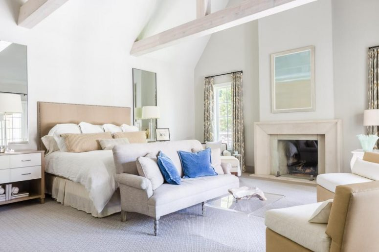 a welcoming neutral farmhouse bedroom with a tan bed, matching nightstands, a vintage loveseat, a fireplace, an acrylic table