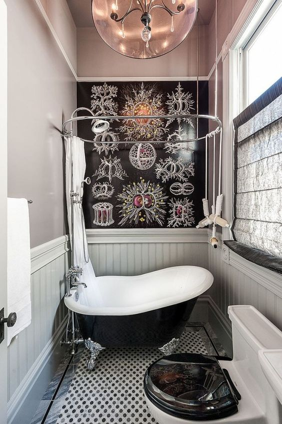 a whimsy bathroom clad with grey plaks and with a catchy floor, a small black bathtub in vintage style and a catchy accent wall