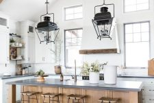 a white and airy famrhouse kitchen with a stained kitchen island, wooden stools, wooden beams and black pendant lamps