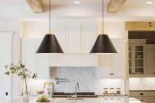a white and grey kitchen with a large kitchen island, white stone countertops, light-stained wooden beams and black pendant lamps
