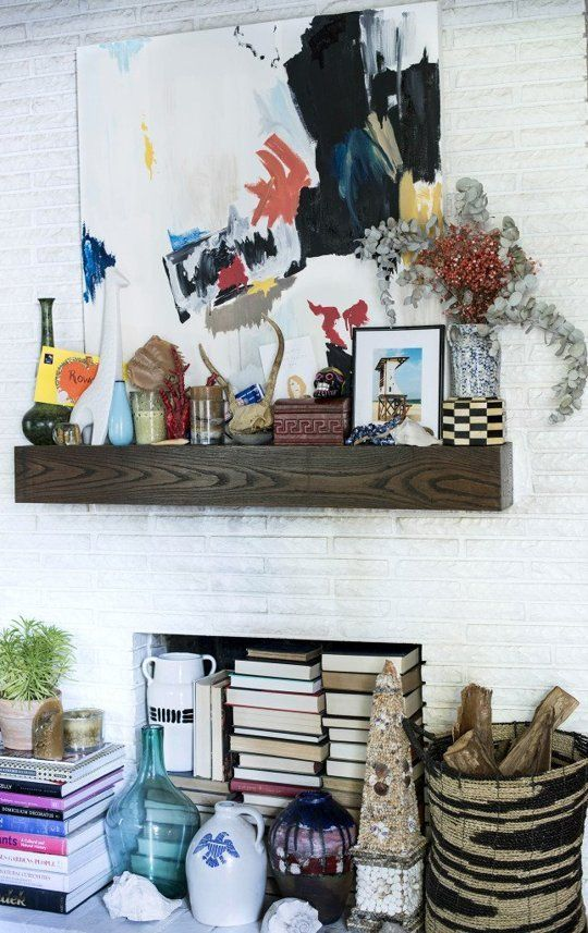 a white brick built-in fireplace with a wood slab mantel, with lots of books inside and candles and various art on the mantel is a stylish idea