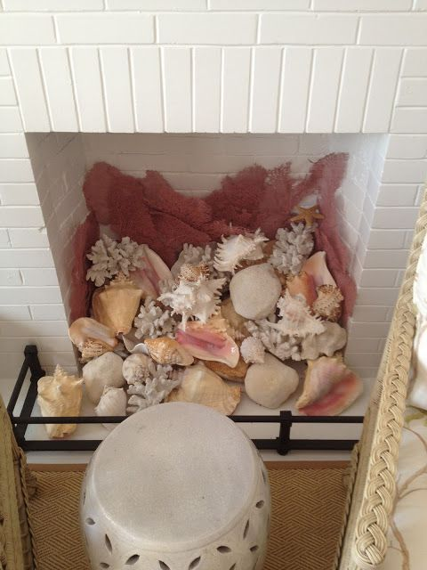 a white brick fireplace filled with lots of various seashells and corals is a great idea for any coastal or seaside home