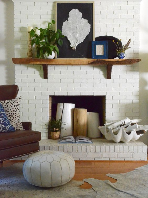 a white brick fireplace styled with tree stumps, a potted plant, a large seashell with whitewashed driftwood for summer