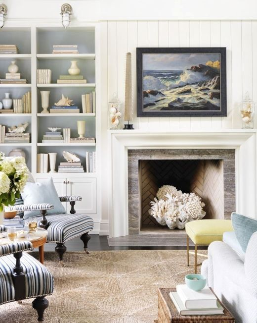 a white coastal living room with built-in shelves and a storage unit, a fireplace with a giant seashell and corals, light blue and striped furniture
