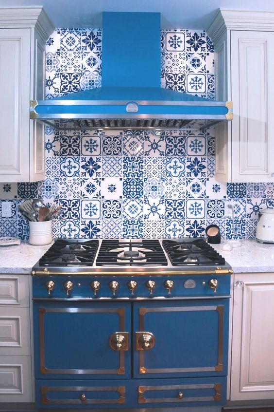 a white cottage kitchen with shaker cabinets, a bold blue cooker and a matching hood, bright blue Moroccan tiles on the backsplash