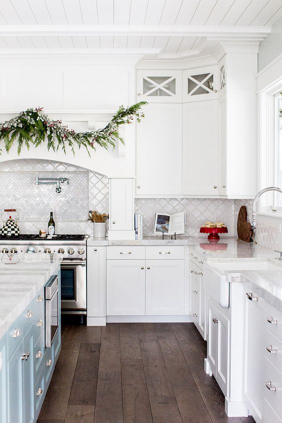 a white farmhouse kitchen with a pale blue kitchen island, a white arabesque tile backsplash and chevron tiles over the cooker is a lovely idea
