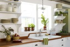 a white farmhouse kitchen with butcherblock countertops, open shelves, green touches and reclaimed wooden beams on the ceiling