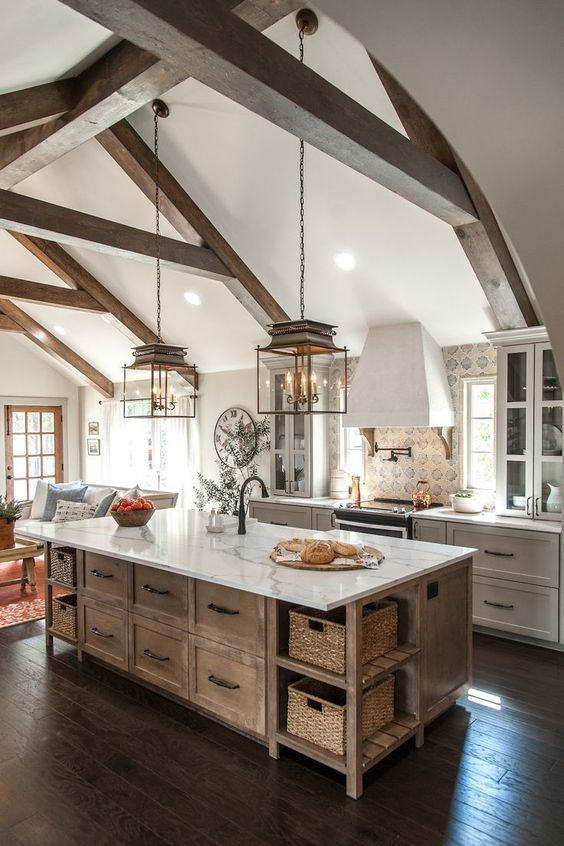 a white farmhouse kitchen with shaker cabinets, a stained kitchen island, wooden beams and elegant pendant lamps hanging down
