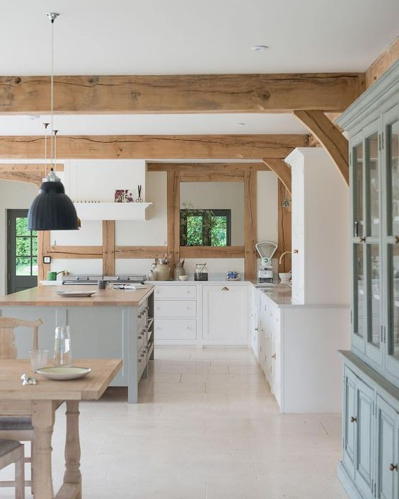 a white farmhouse kitchen with shaker cabinets, white stone countertops, a light aqua kitchen island, wooden beams on the ceiling