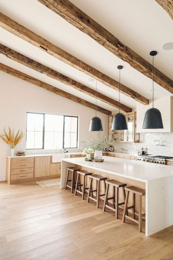 a white farmhouse kitchen with stained cabinets, a stained kitchen island and stools and stained wooden beams