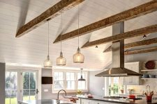 a white farmhouse kitchen with weathered wooden beams, white shaker cabients and a large kitchen island, an additional one with an eating zone