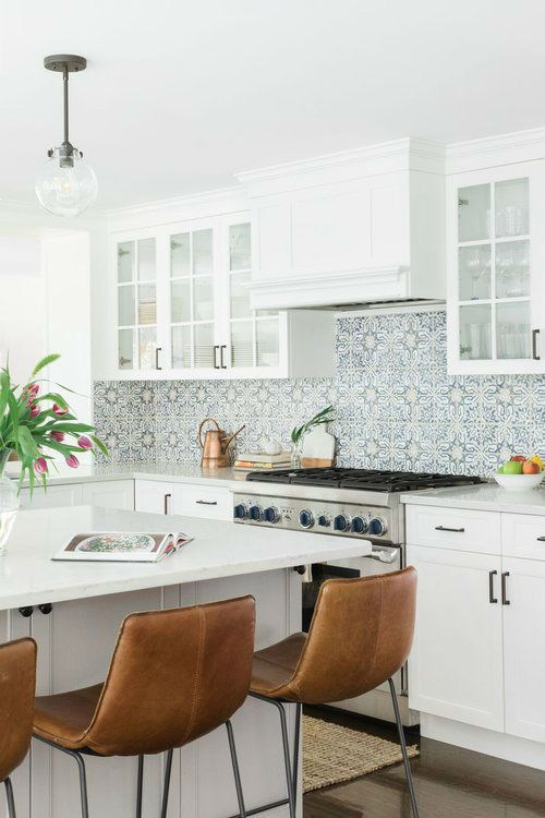 a white farmhouse kitchen with white stone countertops, a blue Moroccan tile backsplash and leather stools is amazing