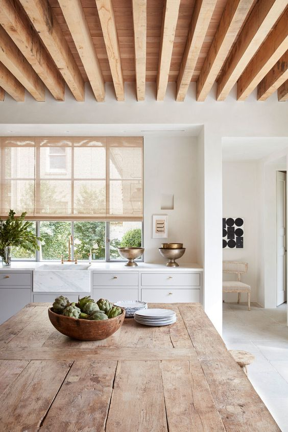 a white farmhouse kitchen with wooden beams on the ceiling, a stained table as a kitchen island plus lots of greenery