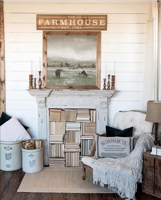 a white farmhouse space with planked walls, refined furniture, buckets with firewood and a shabby chic fireplace used for storing books