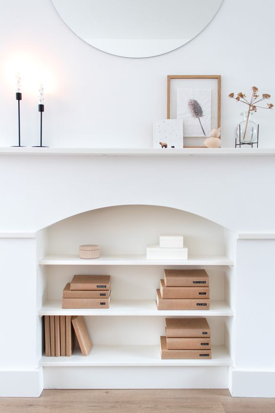 a white faux fireplace used for book storage, minimalist mantel decor with candles, herbs and a botanical artwork