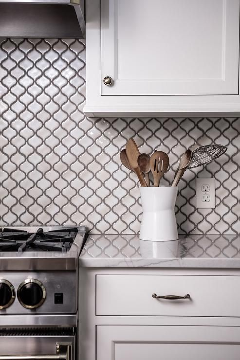 a white kitchen paired up with a white small scale arabesque tile backsplash, white stone countertops and polished fixtures and appliances