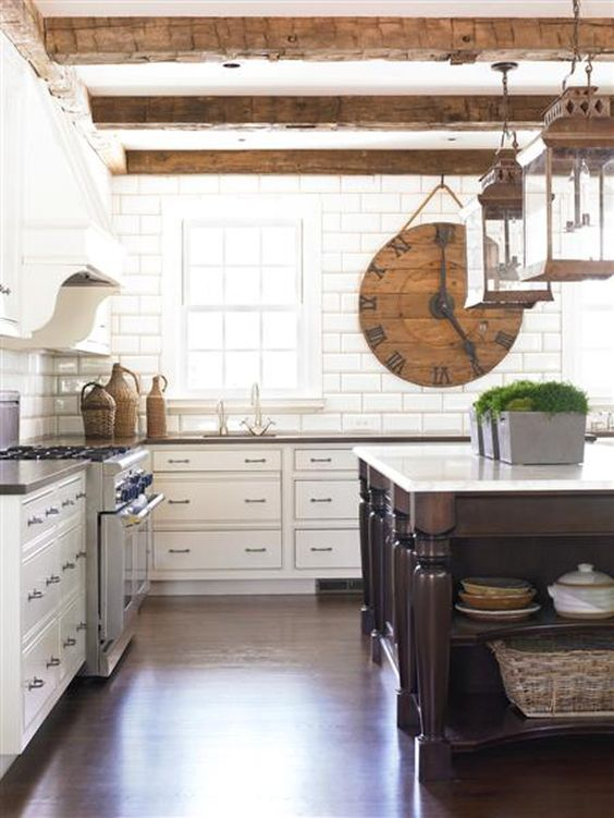 a white kitchen with a subway tile backsplash, weathered wooden beams, a dark stained kitchen island and greenery